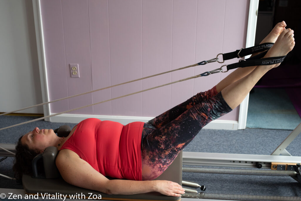Zoa on the Pilates Reformer with feet in straps