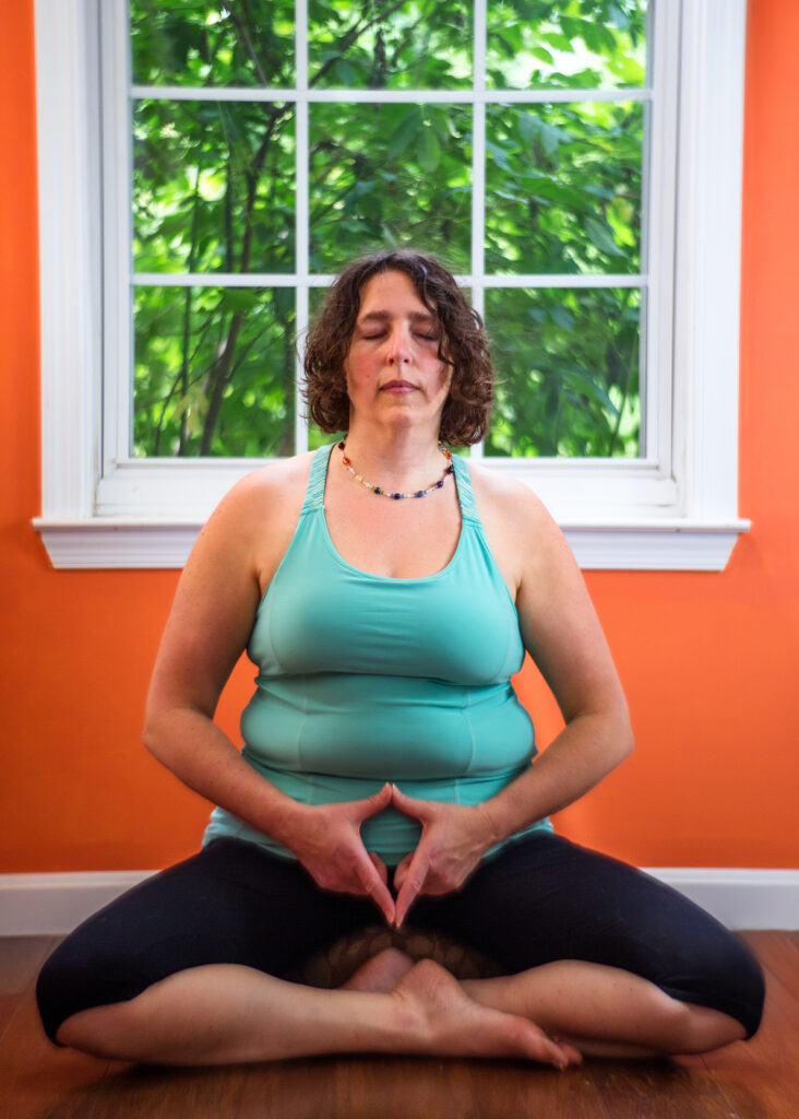 Zoa in a meditative pose with hands showing yoni mudra