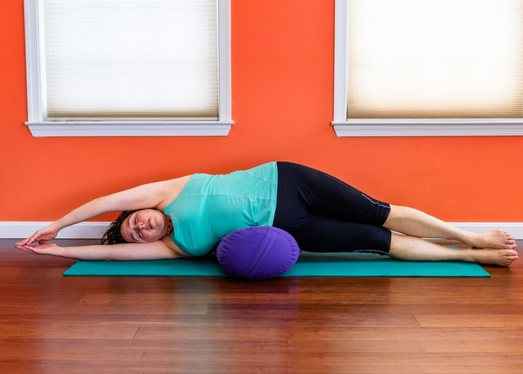 Zoa in yoga pose: Side Lying Crescent Moon with Bolster
