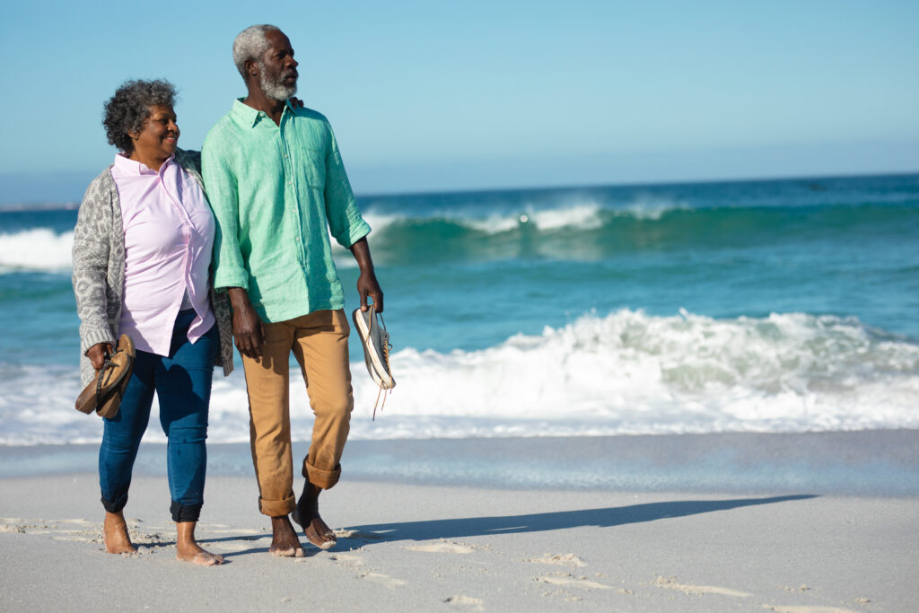Old Couple walking barefoot on the beach